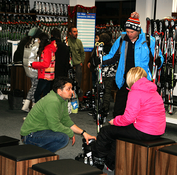 choosing ski boots at ski & board traventuria rental shop, bansko